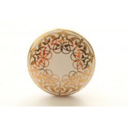 Biały uchwyt do mebli ze złotym ornamentem